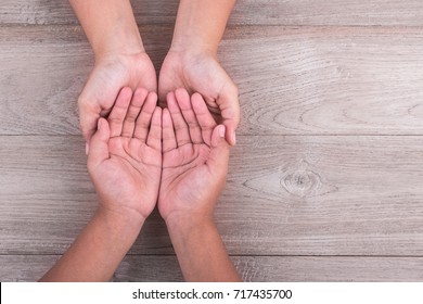 Help and support Concept : Woman holds her young kids hands on brown wooden table background. Free space for text or design