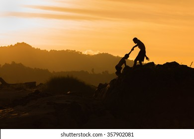 Help, support, Silhouette, mountain at sunset, one of them giving hand and helping to climb. Silhouette of helping hand on mountains in sunset background.