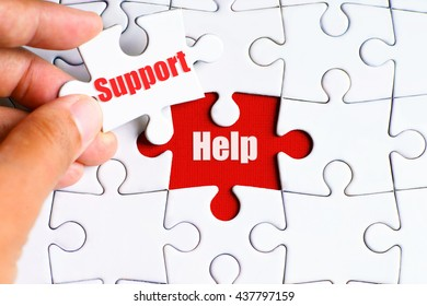 """""""Help"""" text on missing puzzle with a hand hold a piece of """"Support"""" text puzzle want to complete it - business and finance concept"""