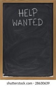 help wanted advertisement handwritten with white chalk on blackboard, copy space below, eraser smudges