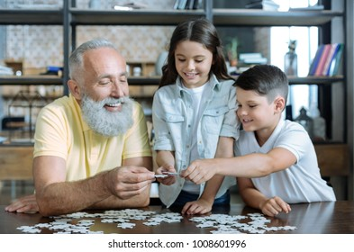 Help is what really matters. Selective focus on hands of a retired gentleman and his grandkids smiling and chatting while working on a puzzle picture together.