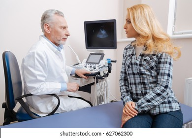 Helpful aged practitioner communicating with patient at work