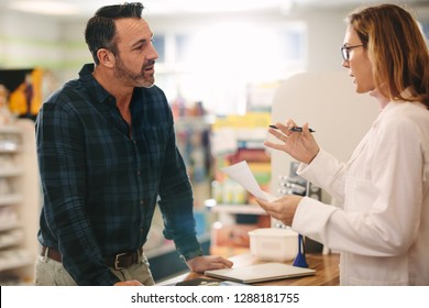 Helpful female druggist dealing with a male customer standing at her desk in the pharmacy. Pharmacist explaining a prescription to customer.