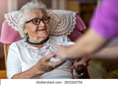 Hilfreiche Krankenschwester gibt einer älteren Frau eine Tasse heißen Tee