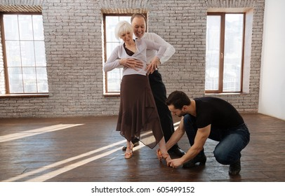 Helpful mature dance instructor teaching aged couple in the ballroom