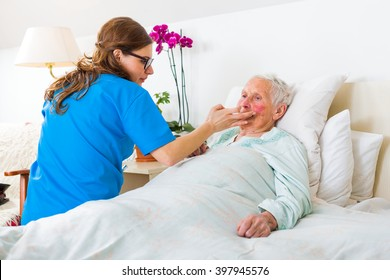 Helpful nurse caring for the senior woman in the nursing home.