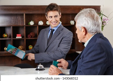 Helpful receptionist in hotel showing city map to senior guest