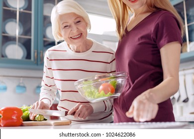 Helpful technology. Charming young woman and her elderly mother making a vegetable salad and checking the recipe on a tablet while smiling