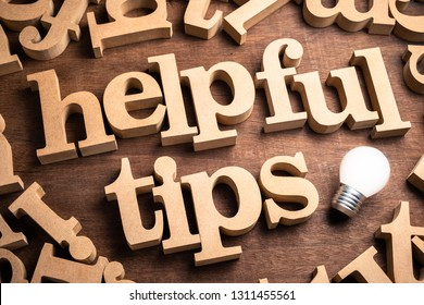 HELPFUL TIPS in scattered wood letters on the table with glowing light bulb