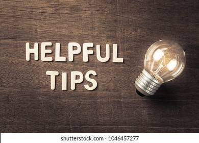 Helpful Tips text with glowing light bulb on wood texture