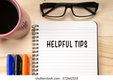 HELPFUL TIPS text on notebook with cup of coffee and glasses on wooden background.