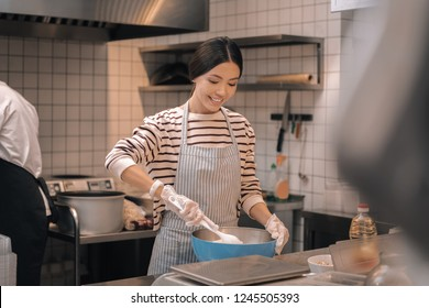 Helpful worker. Helpful young appealing worker of restaurant helping chef cooking in kitchen