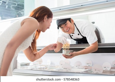 Helpful young sales assistant smiling at a customer through the glass of the display counter as he leans forwards to serve her selection of food