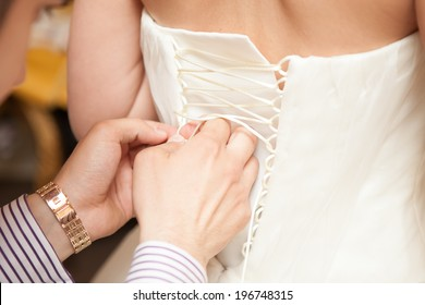 Helping the bride to put her white wedding dress on