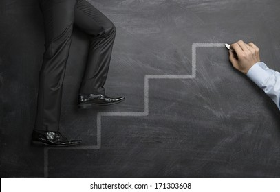 A helping hand, businessman climbing the career steps drawn on a black chalkboard
