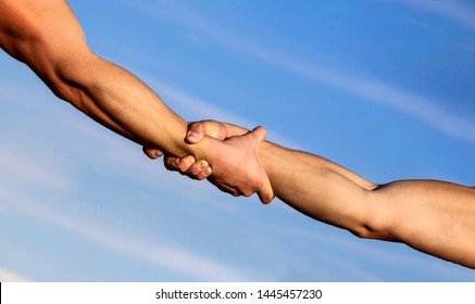 Helping hand concept and international day of peace, support. Two hands, helping arm of a friend, teamwork. Hands of on blue sky background. Helping hands concept, support. Close up help arm.