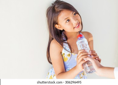 helping hand giving a bottle of water to poor child