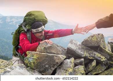Helping hand - hiker man getting help on hike smiling happy overcoming obstacle. Hikers climbing on rock, mountain at sunset, one them giving hand and helping to climb. Help, support Concept teamwork.
