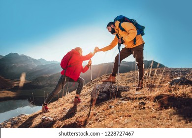 Helping hand - hiker woman getting help on hike happy overcoming obstacle.