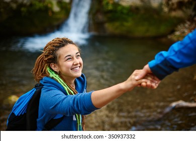 Helping hand - hiker woman getting help on hike smiling happy overcoming obstacle. Tourist backpackers walking in autumn forest. Young couple traveling.