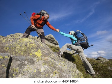 Helping hand - hiker woman getting help on hike smiling happy overcoming obstacle.