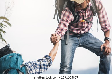 Helping hand outstretched for salvation . Strong hold. Couple hiking help each other in mountains . Two people climbing on mountain and helping.