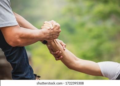 Helfen Sie die Hand ausdehnt für die Rettung . Starker Halt. Coupé Wandern hilft einander in den Bergen . Zwei Leute klettern auf den Berg und helfen.
