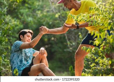 Helfen Sie die Hand ausdehnt für die Rettung . Starker Halt. Running man seinem Freund hilft. Der Mensch hilft einander, auf dem Laufweg zu laufen. Der Trail-Läufer hilft Männern, die von einem Hang weglaufen.