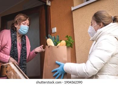 Hilfe beim Einkauf von Nahrungsmitteln während des Ausbruchs der Pandemie. Freiwillig eine ffp2 Maske tragen, während sie Lebensmittel an ältere Frauen liefern. Unterstützung der lokalen älteren Bevölkerung wegen Covid-19-Schließung