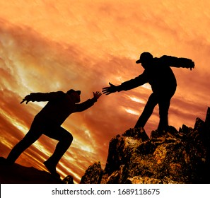 Helping Hand. Take my Hand to Hearten you.Man giving hand a male to help her to climb the mountain. Help concept hand reaching out to help friend in orange sunset sky  background