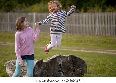 A Helping Hand. A young girl has the help of her older sister as she attempts a jump off an old fallen tree trunk. She is not very old and she is trying very hard to be brave.