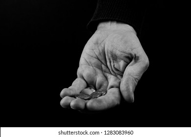 Helping hands concept, Rich giving the poor, Man's hands palms up holding money coins, reaching out, black and white