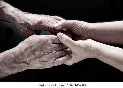 Helping hands, from old man and young woman, care for the eldery people, isolated black