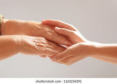 Helping hands on grey background, closeup. Elderly care concept