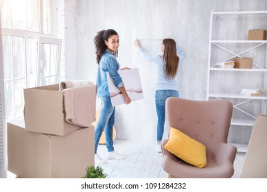 Helping her roommate. Pretty curly-haired girl posing with a picture in her hands while waiting for her roommate to take wall measurements
