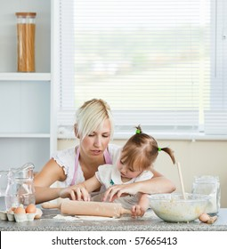 Helping mother and child baking cookies in kitchen
