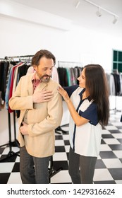 Helping stylist. Smiling cheerful joyful radiant alluring stylist helping a handsome bearded attractive man while trying on a new beige blazer.