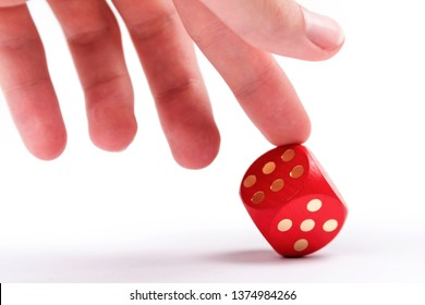 Helping your luck, cheating in games, dishonesty concept. A human finger pushing over a dice to make it show a six. Unfair ace in the sleeve, cheater, uneven odds in business concept