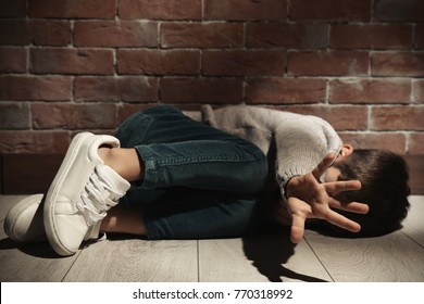 Helpless little boy lying on floor against brick wall. Abuse of children concept