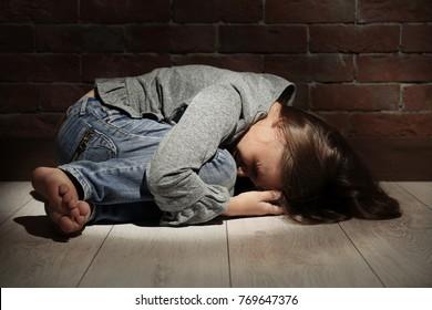 Helpless little girl lying on floor against brick wall. Abuse of children concept