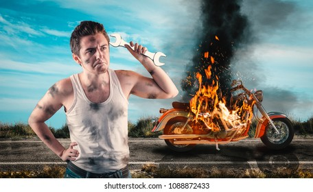 Helpless man holding a wrench with his motorcycle on fire in the background. Needs help to repair the motorbike.