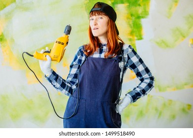 Helpless middle age female worker holds drill in hand.Serious builder woman using electric screwdriver. DIY. Woman in navy blue overalls.She is working at flat remodeling. Building, repair,renovation.