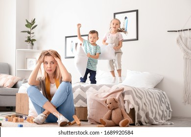 Helpless nanny and naughty little children playing in bedroom