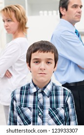 Helpless sad boy staying in front of his parents whom are getting divorced