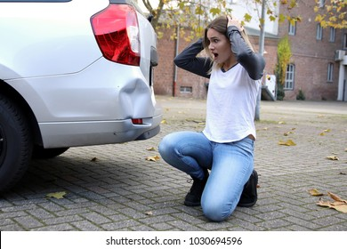 Helpless woman looking at her damaged car