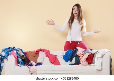 Helpless woman standing behind on sofa couch in messy living room shrugging. Young girl surrounded by many stack of clothes. Disorder and mess at home.