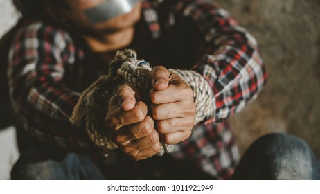 Helpless young man hands tied with rope, Missing kidnapped, Hostage, human trafficking and violence concept