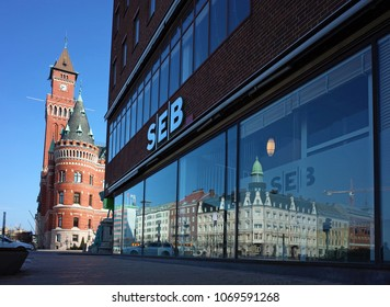 Helsingborg, Sweden - 14 April, 2018: Big windows of SEB bank building view from Jarnvagsgatan street with clock tower of Town Hall