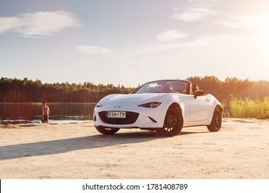 Helsinki, Finland 19 July 2020 Mazda MX-5 Cabrio is the fourth and current generation. White Mazda Roadster stands on beach in sunset with background landscape. Open roof, Summer mood Man  swimming.