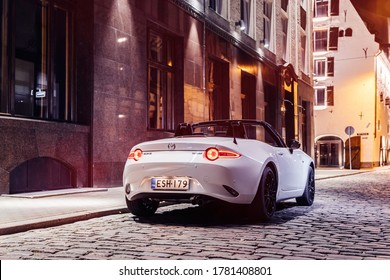 Helsinki, Finland 19 July 2020 Mazda MX-5 cabrio is the fourth and current generation of the Mazda MX-5. White Mazda Roadster stands on road with open roof in night time, background cityscape.